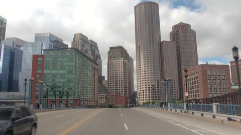 FPV, CLOSE UP: Traveling towards high glassy window pattern skyscrapers in Downtown Boston financial district skyline, USA. Driving on busy highway in metropolitan city overlooking office buildings