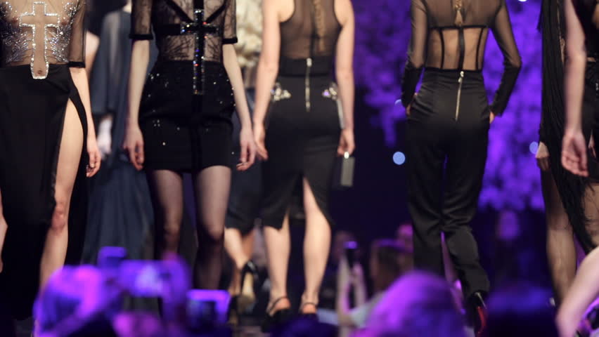 Female models walk the runway in beautiful black dresses during a Fashion Show. Fashion catwalk event showing new collection of clothes. Unrecognizable people. Legs only.