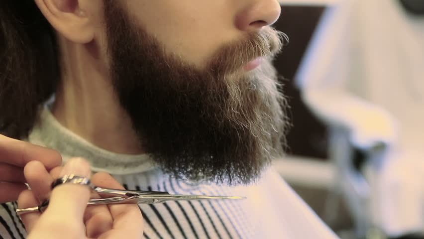 Barber combing beard with a pair of scissors at a barber shop | Shutterstock HD Video #25471073