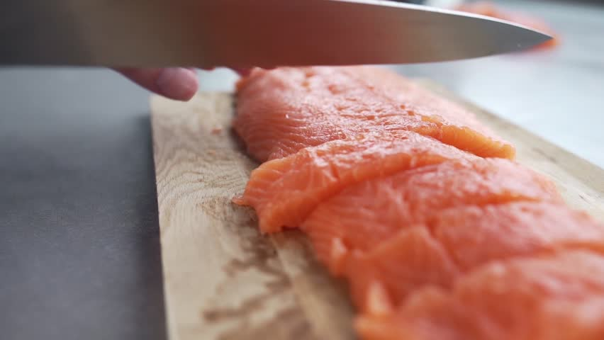 The cook cuts salmon fillet, chef prepares fish for cooking, dishes with fish, diet and healthy food