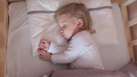 Peaceful adorable baby sleeping on his bed in a room at home. Soft focus. Sleeping baby concept. 2 year-old babyboy sleeps at home, top view