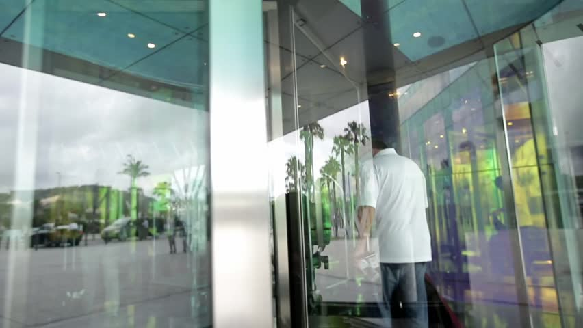 People using automatic revolving glass door or entering rotating spinning glass doorway. Entrance to the & People Walking Through A Revolving Door Stock Footage Video ...