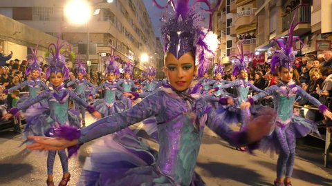 Young kids dancers dressed purple parade during Carnival of Aguilas with costumes and feathers. A party with international tourist interest. Aguilas, Spain February 26th, 2017.