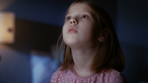 Curious Little Girl in Her Bedroom at Night, Stands on Tiptoe and Looks out of the Window. Shot on RED EPIC-W 8K Helium Cinema Camera.