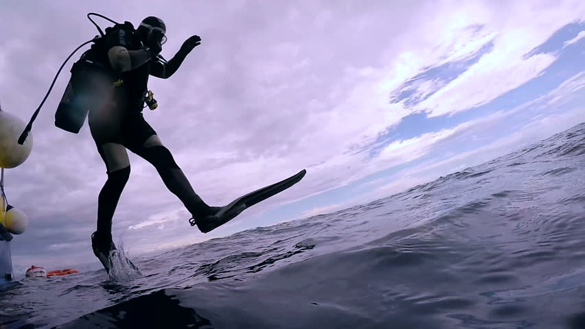 Scuba Diver Jumping into the Ocean. In slow motion a scuba diver jumps into water.  Scuba Diver Jumping Off Dive Boat.