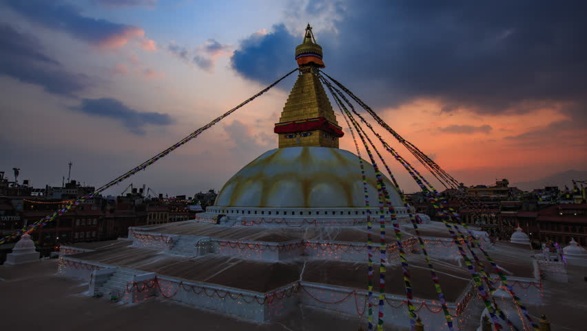 Time lapse day to night of Prayer flags flying on the Boudhanath Stupa. symbol of Kathmandu, Nepal.