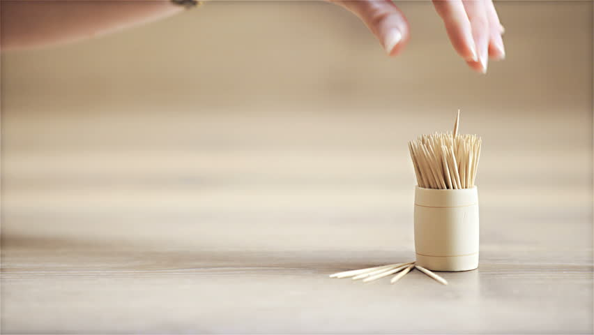 Hand pick wooden toothpick dolly slide 4K. Sliding from left to right with toothpicks in focus and in right part of frame when hand from left side takes a single toothpick.