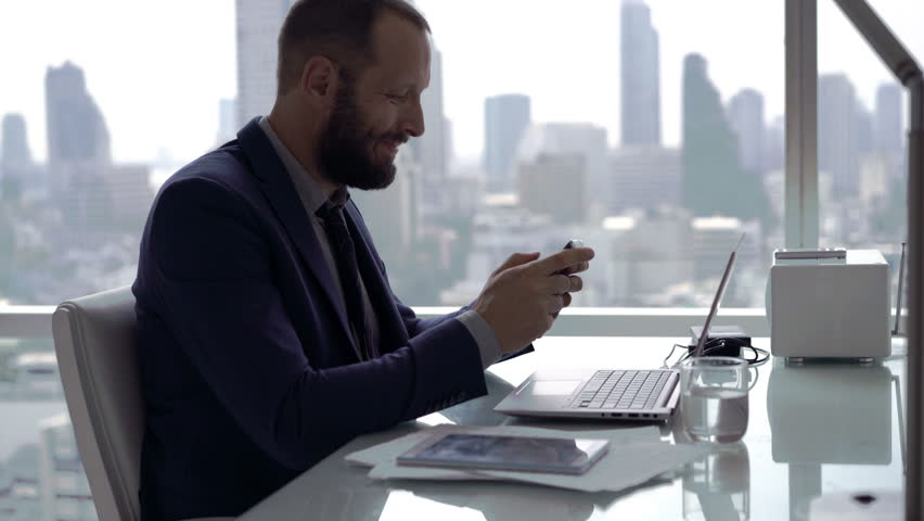 Young businessman playing game on smartphone by table in office, 4K  | Shutterstock HD Video #25584743