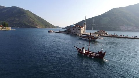 Wooden sailing ship near the island of Our Lady of the Rocks. Aerial Photo drone. Water transport. Montenegro, Bay of Kotor.