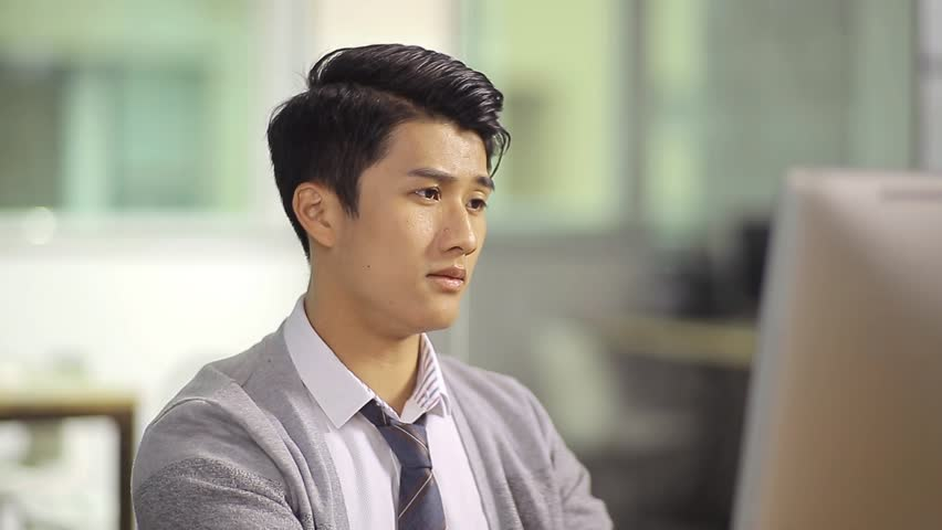 Young asian business executive looking at computer screen thinking.  | Shutterstock HD Video #25601453