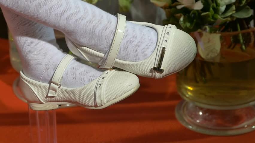 Legs of a little girl in white socks in white shoes
