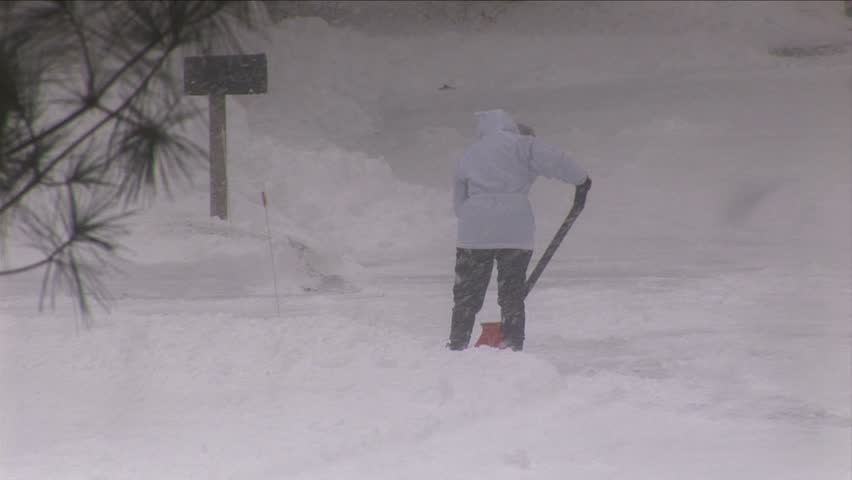 Woman shoveling snow during snowstorm