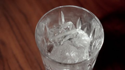 glass with ice filled up with vodka in slow motion