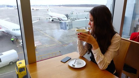 Young adult woman drink coffee at airport cafe, make sip and look to large window. Airliner parked at apron area. Lady spend time before flight, waiting for boarding gate to open