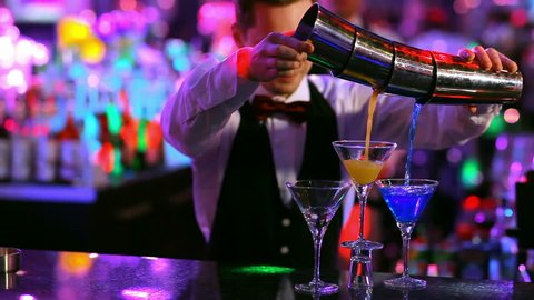 club: a bartender pours colorful cocktails 3 glasses at once.