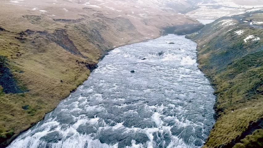Aerial flight with drone over the famous  Skogar waterfall in Iceland. It is located on the South of the island. Image taken with action drone camera causing distortion and blur. Slow motion shot | Shutterstock HD Video #25673333