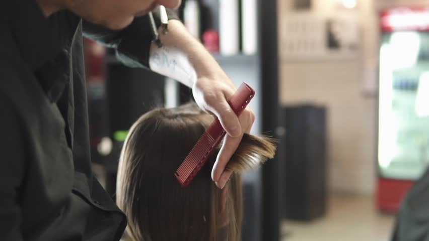 Closeup view of a hairdresser's hands cutting hair with scissors. Young woman getting her hair dressed in hair salon. Hairdresser at work. Beauty saloon. Shot in slowmotion