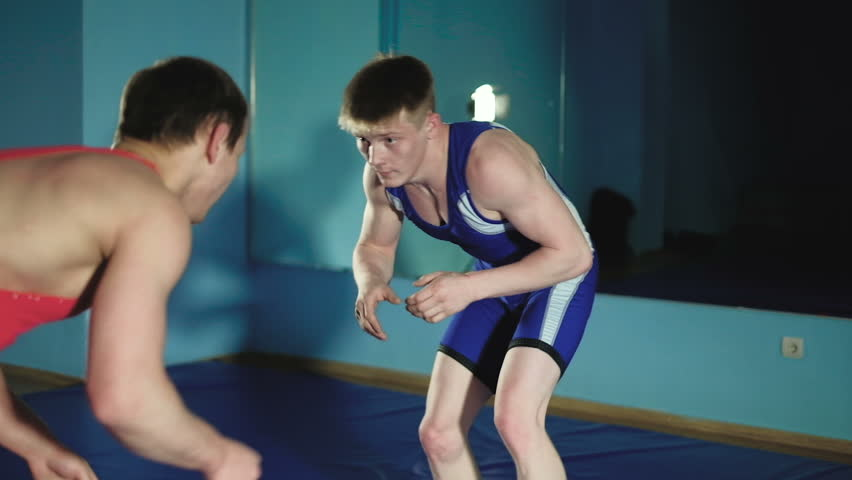 two wrestlers Greco-Roman wrestling on the blue background