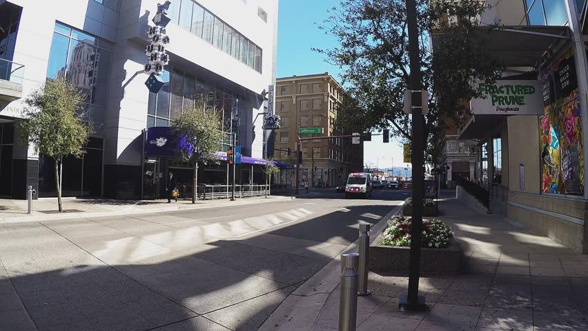 PHOENIX AZ/USA: March 14, 2017- Shot of an ambulance passing camera in downtown Phoenix Arizona. An emergency response vehicle speeds by with loud siren sounds blasting. | Shutterstock HD Video #25693703