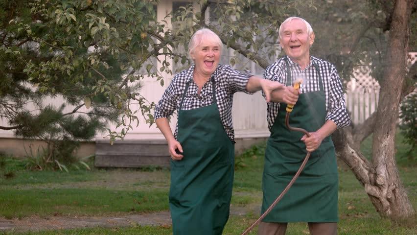 Elderly couple with garden hose. Old people having fun.