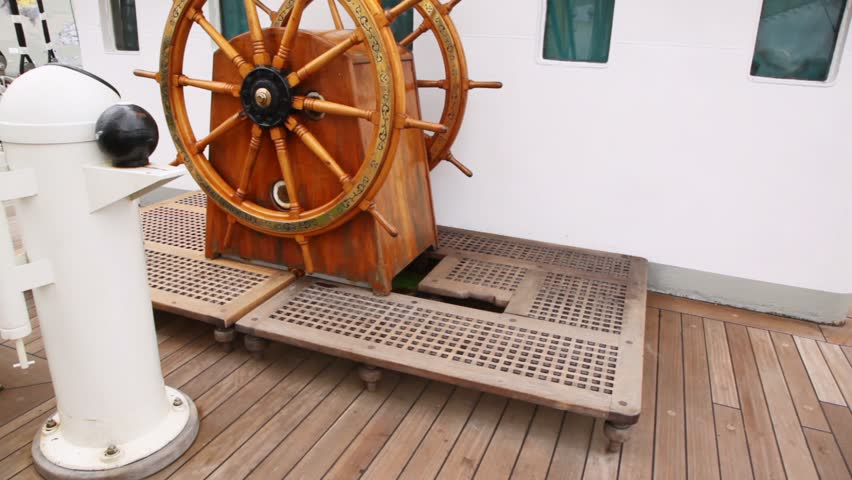 Old steering wheel from wood stands on sailing vessel deck Krusenstern against captain cabin