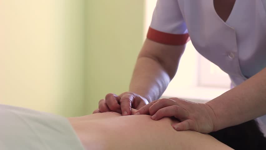 The masseur in a white gown spends a therapeutic back massage in a room with a wall green color. | Shutterstock HD Video #25726925
