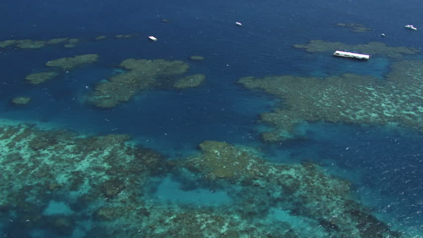 Aerial of the Great Barrier Reef, showing pontoons or snorkeling platforms on the reef