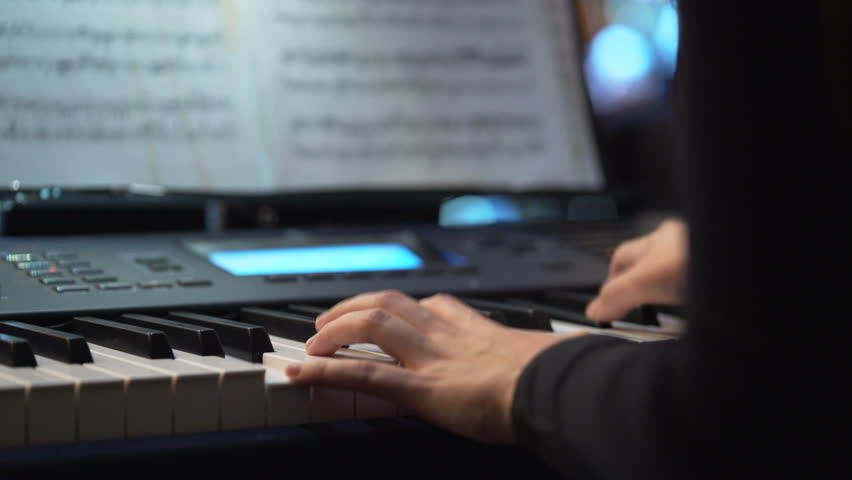 Hands of a pianist who plays keyboardist during a music concert. Keyboards player on stage during concert. Arranger hands playing keyboards concept. close-up | Shutterstock HD Video #25731413