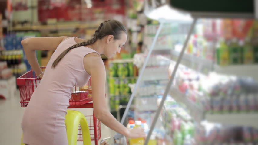 Young attractive woman in dress selecting juice at the supermarket in the refrigerated section | Shutterstock HD Video #25735403