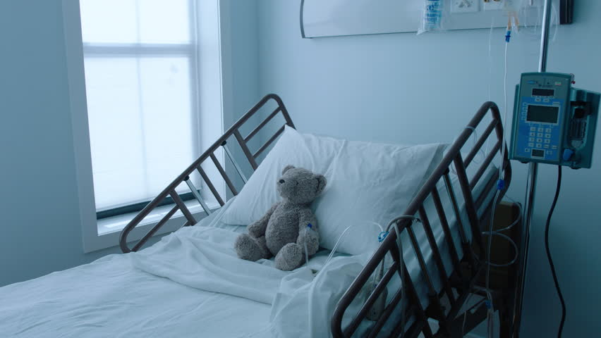 A teddybear stuffed animal with an IV recovering in a hospital bed next to a window, slow motion, 4K | Shutterstock HD Video #25746653