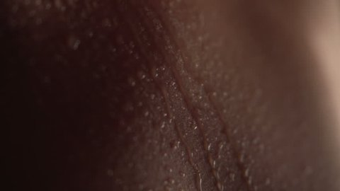 Texture of the skin close-up. Drops of water roll down the body. Young beautiful girl body. Macro