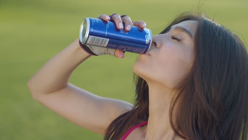Asian woman drinking soda. Sport woman drinking energy drink. Closeup of sporty woman drinking energy drink outdoors