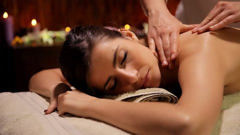 Warm magic atmosphere in luxury spa woman getting shoulder and back massage