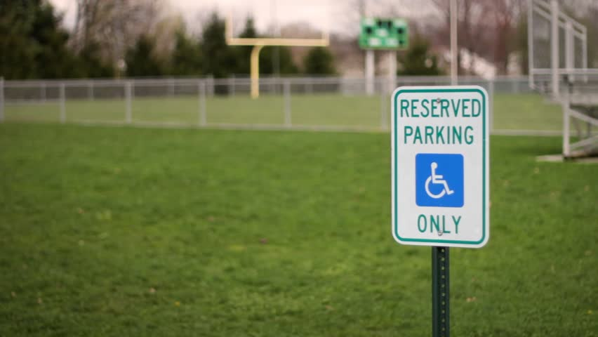 A handicap reserved parking only sign near empty football field