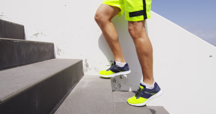 Running on stairs - man doing staircase run in outdoors fitness sport concept. Male runner athlete climbing stairs in sport workout run outside. RED EPIC SLOW MOTION.