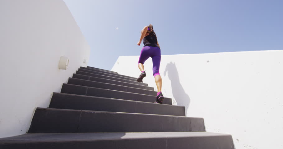 Running on stairs woman doing run up on staircase. Female runner athlete climbing stairs in sport workout run outside. Running shoes and legs close up