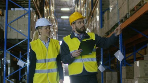 Female Auditor Walks with Male Surveyor Doing Inventory Checking in Warehouse with Big Pallet Racks in it.