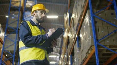 Overseer Wearing Hard Hat with Clipboard Fills in Forms in a Warehouse. He Walks Through Rows of Storage Racks with Merchandise.