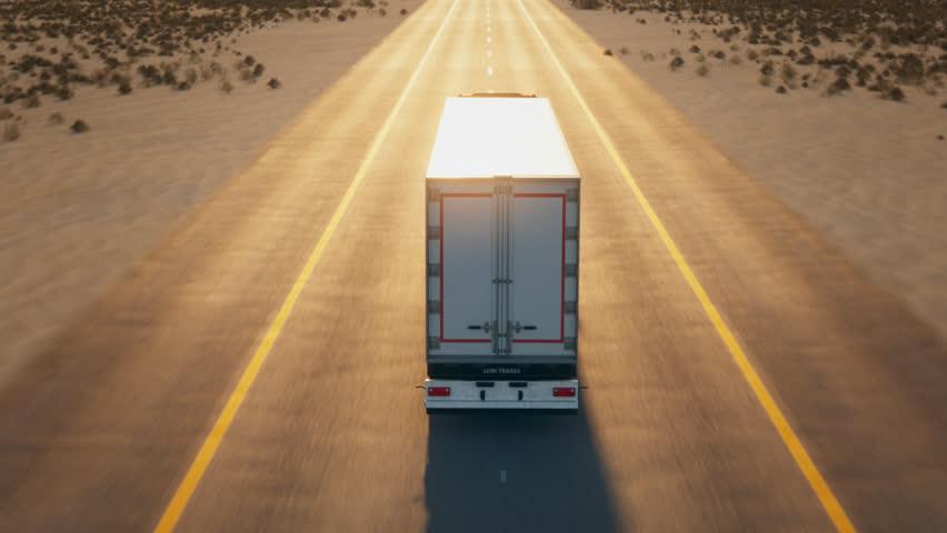 Truck Driving On Asphalt Road At Desert Landscape
