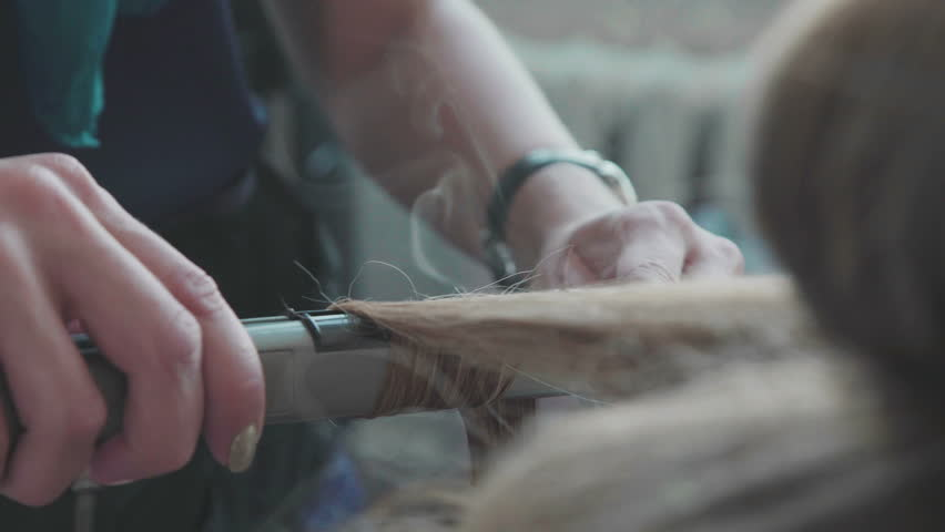 Stylist. Beauty saloon. The stylist winds a strand of hair on the curling iron and then sprinkles the hairspray. The process of creating styling - voluminous curls. | Shutterstock HD Video #25826123