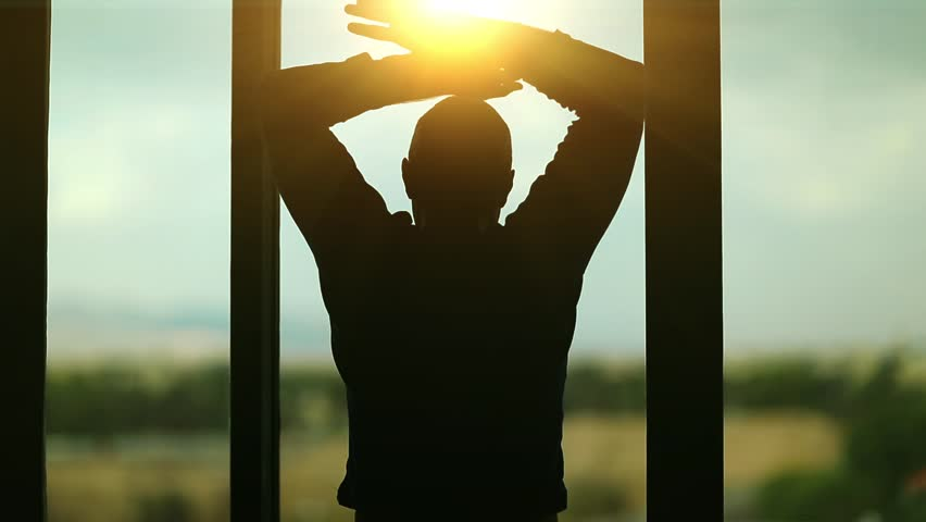 Man opens the curtains in the morning raises his hands and stretch oneself. Young man opens big window curtains and lets the sun light in the room