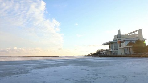 a modern villa on the shore of a frozen river, on the river bank in winter, winter landscape, Blue sky, on the background, View through a frozen river, The sun shines, the sunbeam,