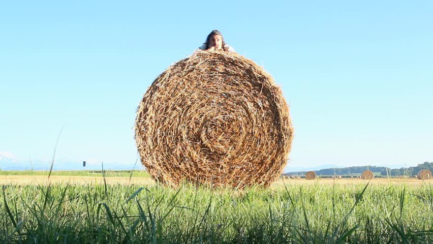 funny man dealing with a hay bale