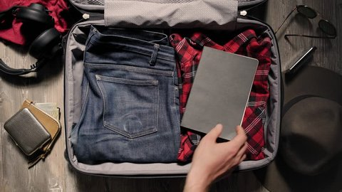 Manly young caucasian with strong arms with tattoos packs his suitcase full of manly artisanal items like selvedge denim, flannel shirt, stainless flask and other hipster accessories
