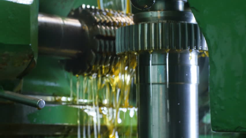 closeup camera moves around green lathe machine with cooling lubricant flowing down metal parts