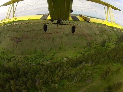 View from the tail of a crop duster as the spray is being applied to the field of wheat