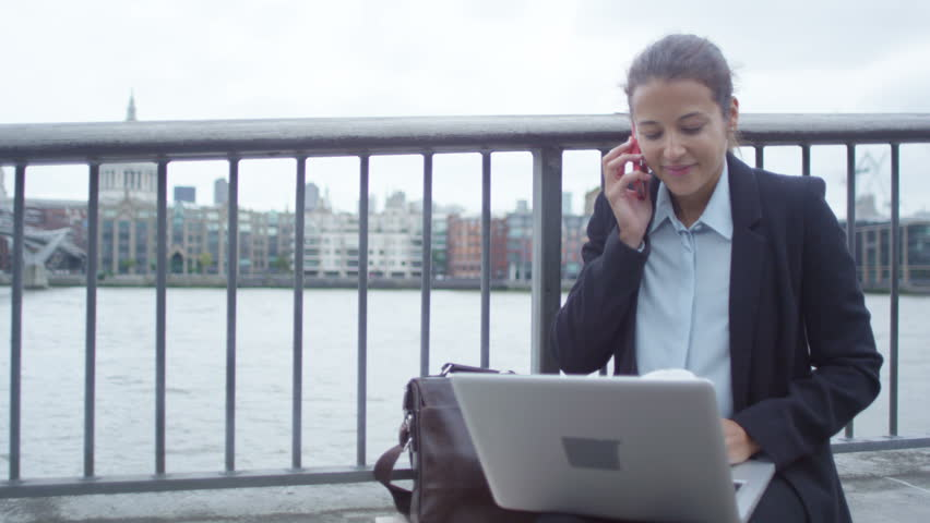 4K Smiling London businesswoman using laptop & talking on phone outdoors in city | Shutterstock HD Video #25874063