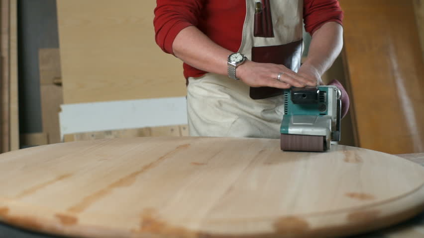 Carpenter slowly moving a polishing machine along the round table in a workshop  | Shutterstock HD Video #25887233