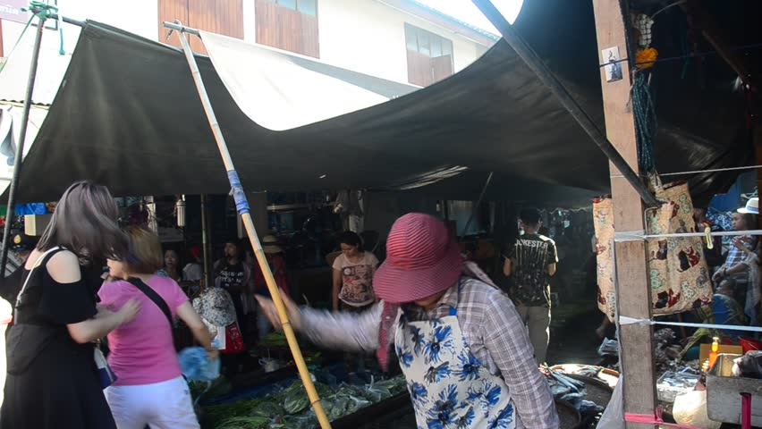 SAMUT SONGKHRAM, THAILAND - APRIL 12 : Travelers people visit and looking Mae klong Railway Market or Talat Rom Hup meaning the umbrella pulldown market on April 12, 2017 in Samut Songkhram, Thailand