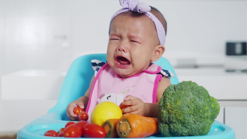 Video footage of a cute female baby crying at home while holding fresh vegetables